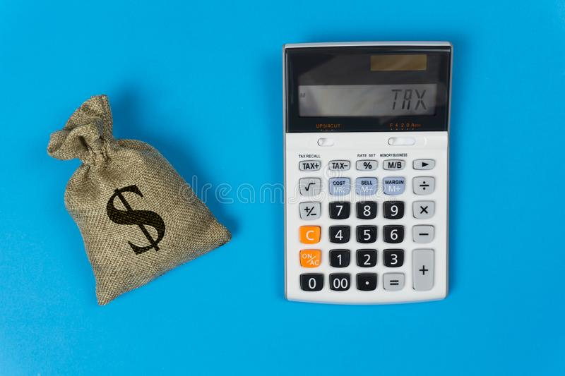 Business and finance taxes concept. A money bag and calculator with text on blue background from top view. Depicts the importance royalty free stock images