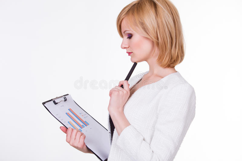 Business, finances and economics - pretty young. Businesswoman holding paper with graph. Female thinking on white background stock photography