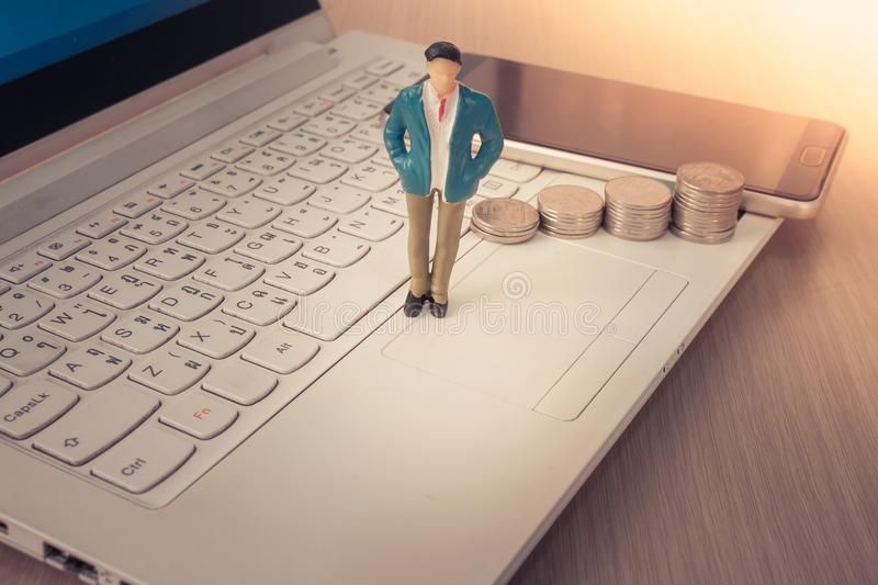 Business man standing on top of stack of silver coins and smartphone with laptop in the background. royalty free stock image