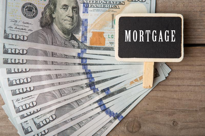 Business and financial concept - one hundred dollar bills and little blackboard with word Mortgage. On wooden background, home, money, estate, house, property stock images