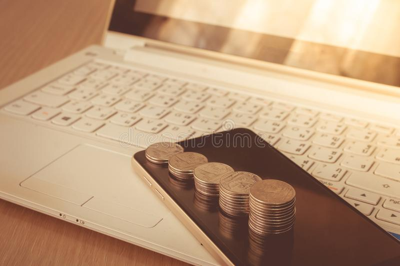 Business and Financial Concept : Stack of silver coins on smartphone with laptop in the background. stock photos