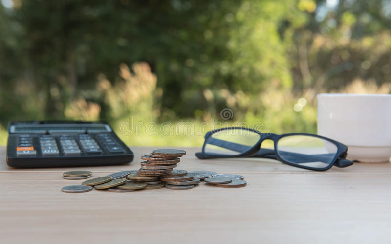 Business on financial report . Closeup coin and banknotes and Calculator , cup on wooden table. Business on financial report . Closeup coin and banknotes and royalty free stock photo