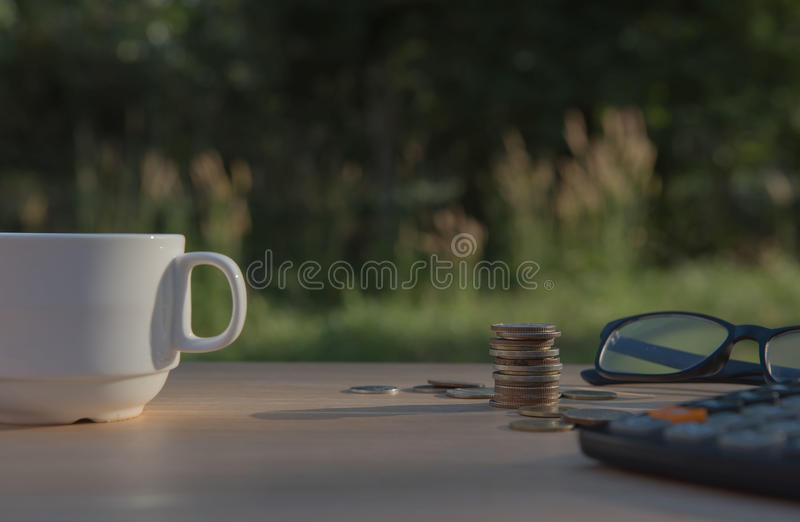 Business on financial report . Closeup coin and banknotes and Calculator , cup on wooden table. Business on financial report . Closeup coin and banknotes and stock photography
