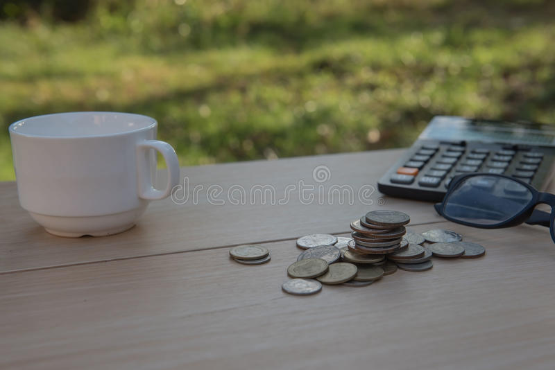 Business on financial report . Closeup coin and banknotes and Calculator , cup on wooden table. Business on financial report . Closeup coin and banknotes and stock photos