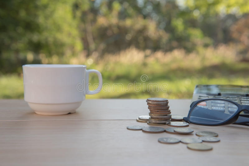 Business on financial report . Closeup coin and banknotes and Calculator , cup on wooden table. Business on financial report . Closeup coin and banknotes and stock images