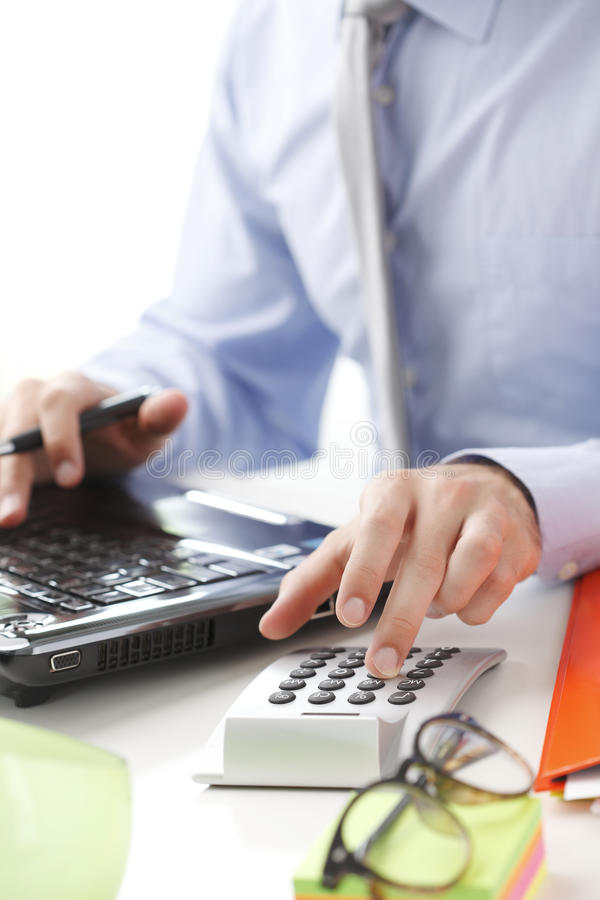 Business financier working at bank. Financial adviser calculating datas while working at bank royalty free stock photography