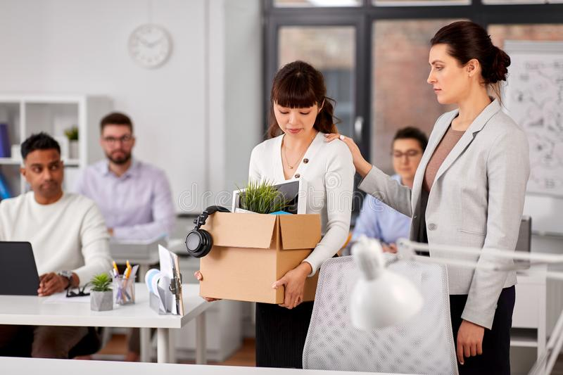 Colleague seeing off fired employee leaving office royalty free stock photo