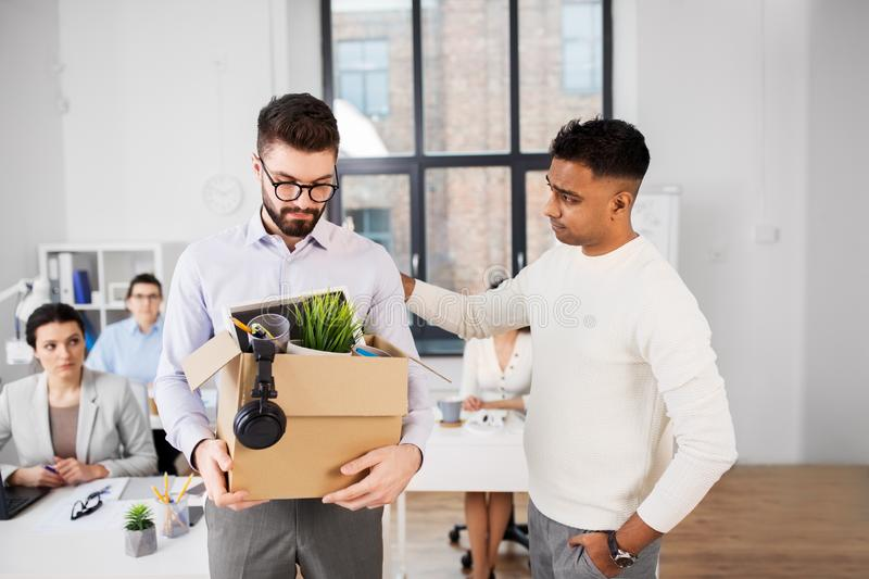 Colleague seeing off sad fired male office worker royalty free stock images