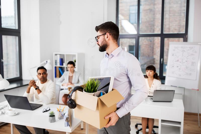 Sad fired male office worker with personal stuff stock photos