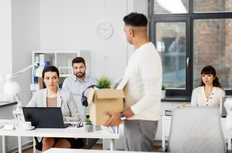 Sad office workers looking at fired colleague stock photo