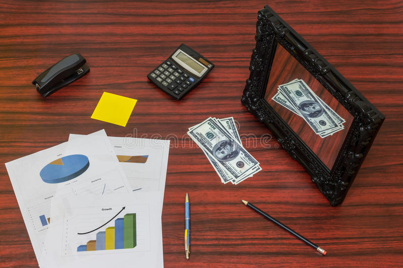 Business flat lay. Sheet of paper with printed graphs on a desk with pen, pencil and calculator around it royalty free stock photography