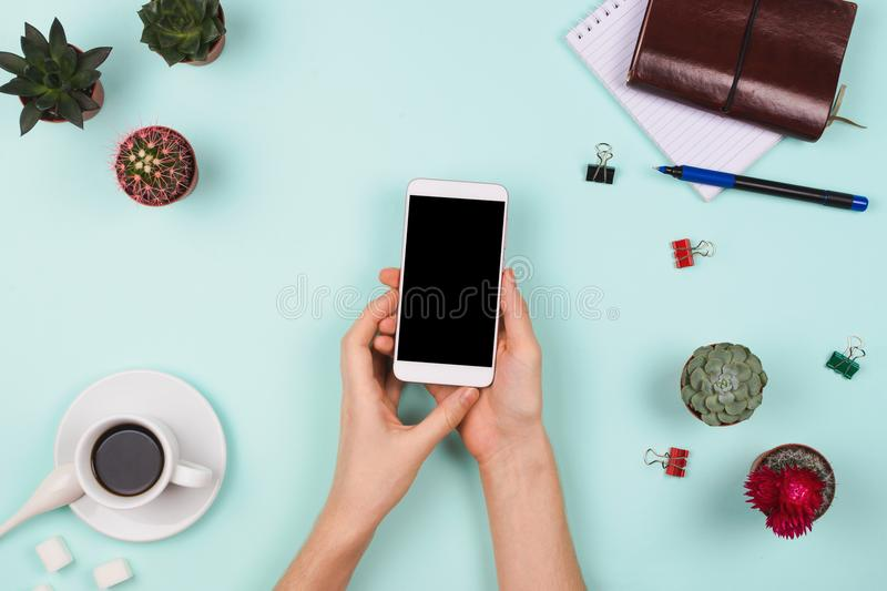 Business flatlay arrangement with woman`s hands holding smartphone with black copyspace and other stationary and office accessori. Es. Mint background. Business stock photography