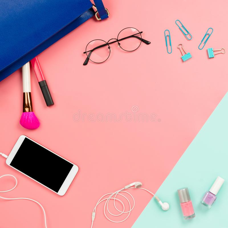 Business frame flatlay with woman`s blue bag, glasses, smartphon. E with black copyspace, cosmetics and stationary supples. Pastel pink and mint background stock images