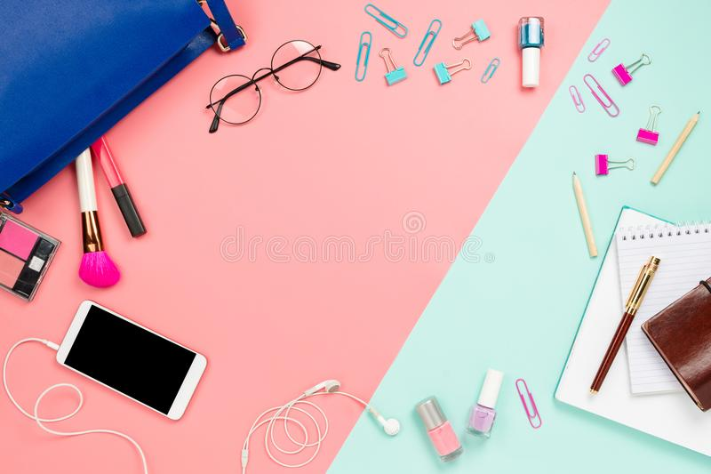 Business frame flatlay with woman`s blue bag, glasses, smartphone with black copyspace, cosmetics and stationary supples. Business frame flatlay with woman`s stock photography