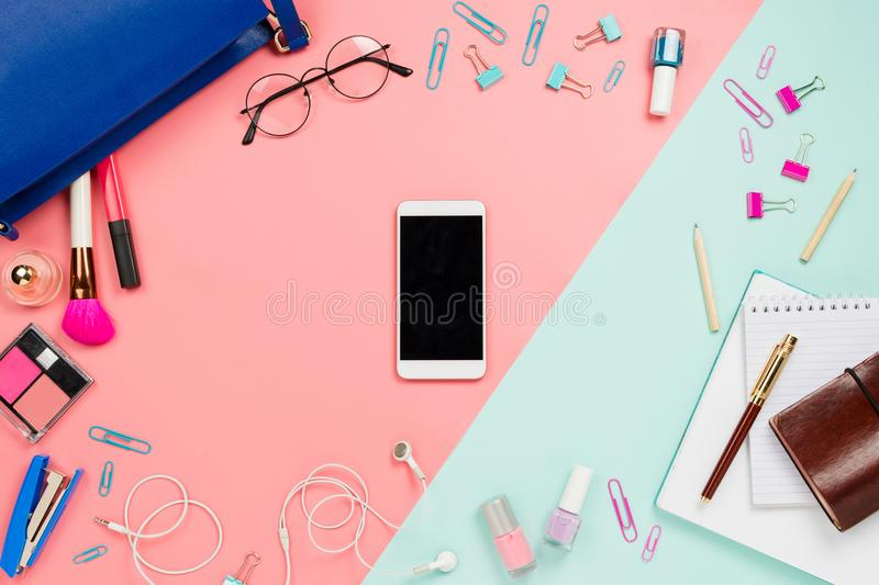 Business frame flatlay with woman`s blue bag, glasses, smartphone with black copyspace, cosmetics and stationary supplies. Pastel pink and mint background stock photography