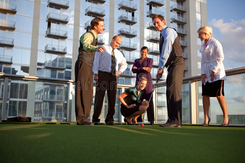 Business fun. Business workers playing golf outside office, having fun stock photography