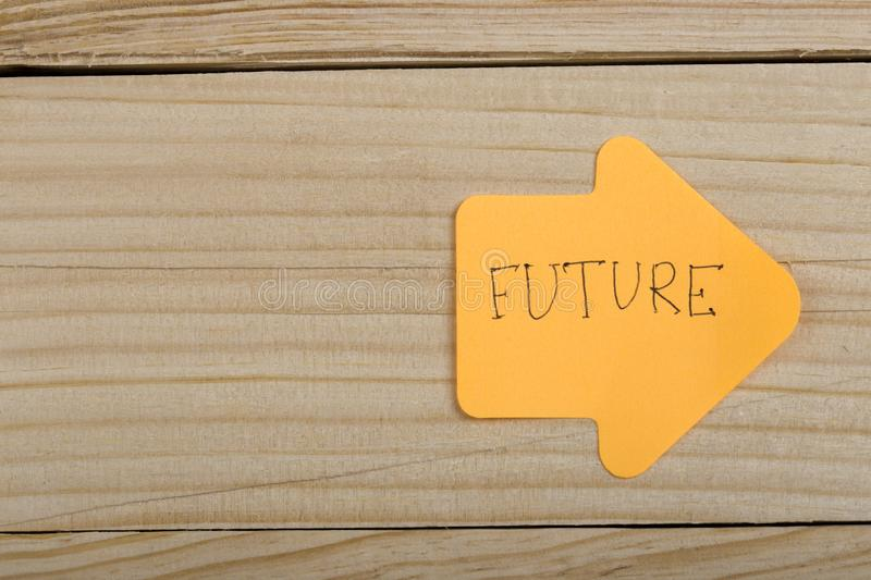 "Business, future and motivation concept - orange sticker and text ""Future"" in the shape of an arrow. On wooden background, paper, label, note, sticky stock photography"