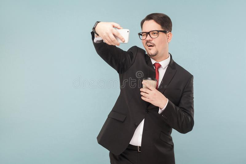 Business, gadgets,technologies. Man making selfie. Indoor, studio shot, isolated on light blue or gray background stock photos
