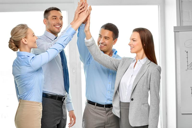 Happy business team making high five at office royalty free stock photo