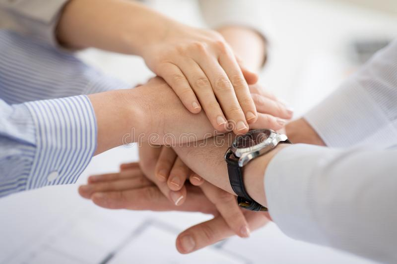 Close up of business team stacking hands stock photography