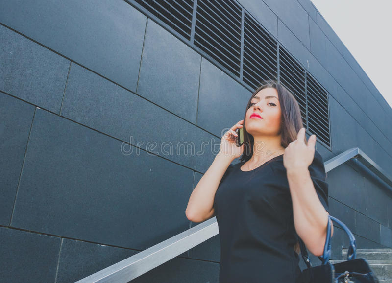 Business girl in black talking on the phone royalty free stock images