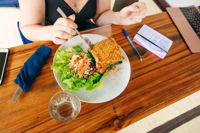 Girl eating vegan lasagna in the cafe royalty free stock image