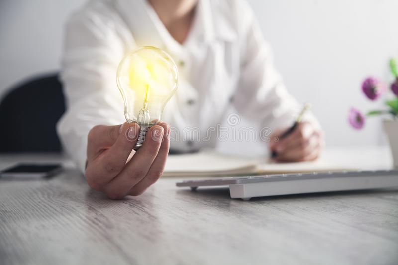 Business girl holding light bulb in office desk. Idea royalty free stock image