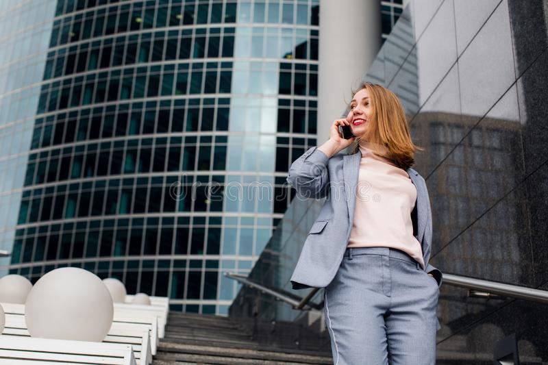 Business girl talking on the phone at office building in the city stock photo