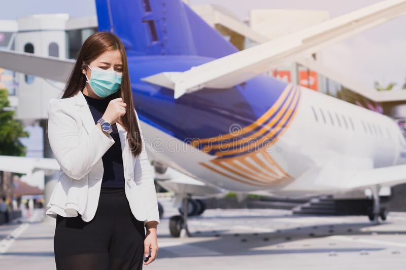 The business girl wearing mask for protecting coronavirus and pm 2.5 and she coughing flu from coronavirus and stnding in front of. Airplane. Coronavirus and royalty free stock photography