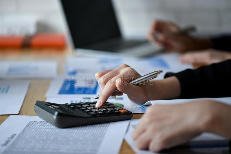 Business girl working with calculator on the desk in office royalty free stock photography
