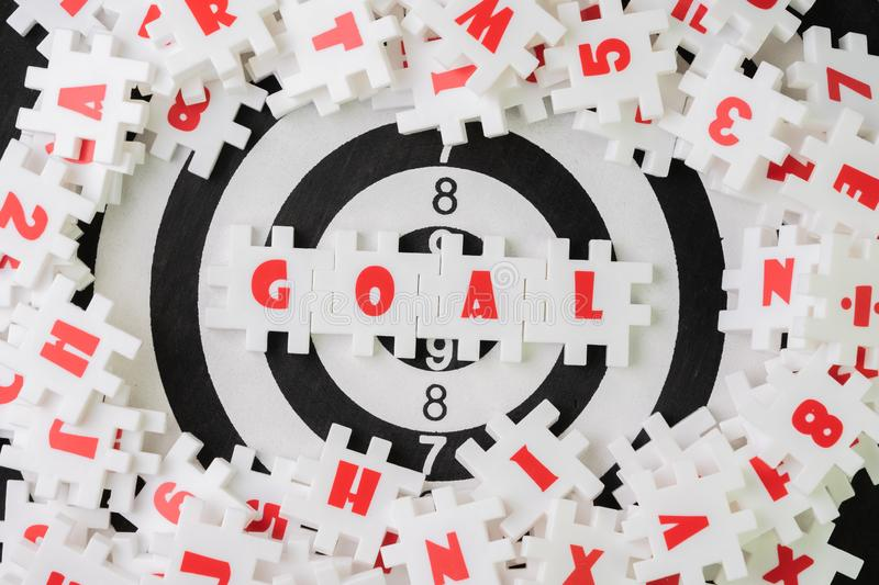 Business goal or target plan for success strategy concept, white puzzle jigsaw with alphabet word GOAL at the center on dartboard royalty free stock images