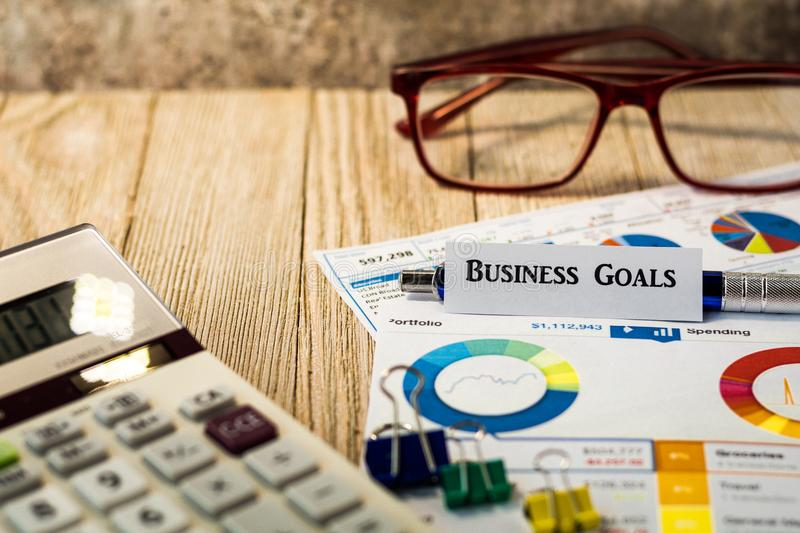 Business Goals finance and investment concept with charts and graphs on wooden board. Investment Strategy motivational finance budget concept with charts and stock images