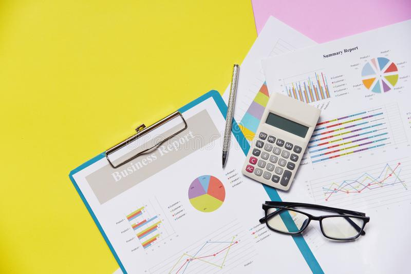 Business graph chart report paper financial document with calculator pen and glasses yellow royalty free stock image