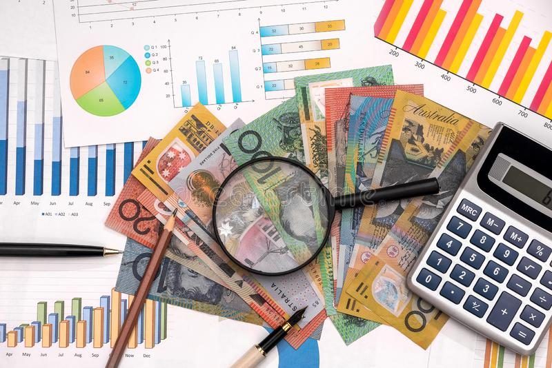 Business graphs with australian dollars, magnifier, pen and calculator.  stock photography