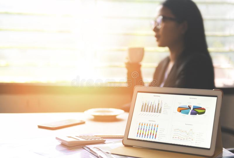 Business graphs chart on a tablet computer technology on the table and woman working in office with coffee cup - Sale report money stock photo
