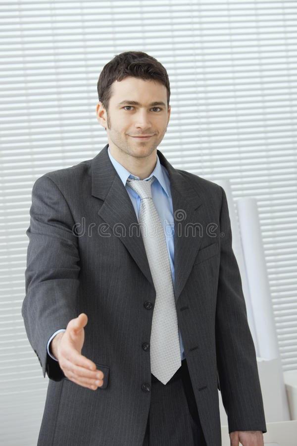 Business greeting. Young businessman in grey suit and blue shirt, standing with open hand, ready to set a deal stock image