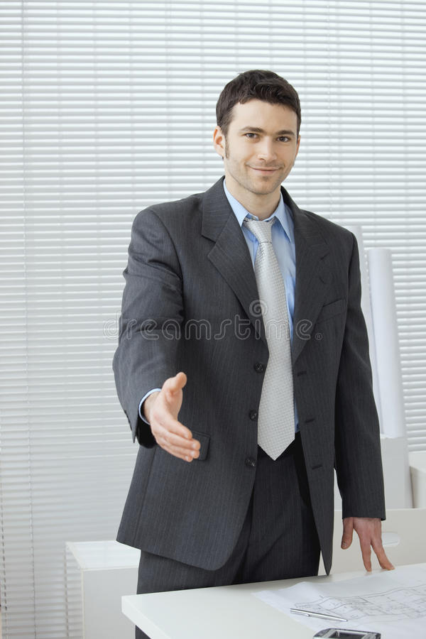 Business greeting. Young businessman in grey suit and blue shirt, standing with open hand, ready to set a deal stock photography