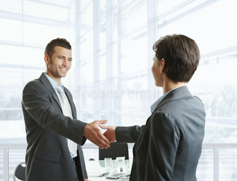 Business greeting. Smiling businessman greeting businesswoman with handshake before meeting royalty free stock photography
