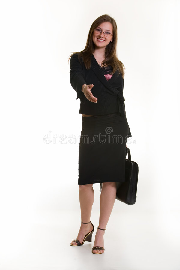 Business greeting. Attractive Business woman offering her hand for a handshake full body dressed in professional business suit and holding a briefcase standing