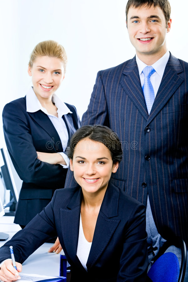 Business group. Portrait of group of three successful business people looking at camera and smiling stock photography