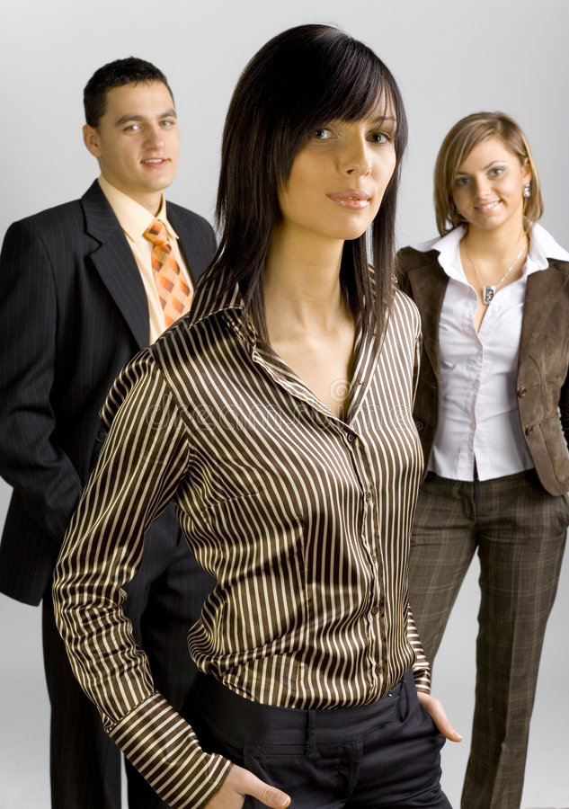 Business Group with Female Leader. Two women and a man are standing and looking at the camera. There's woman-leader at the front of group in the middle. Vertical stock images