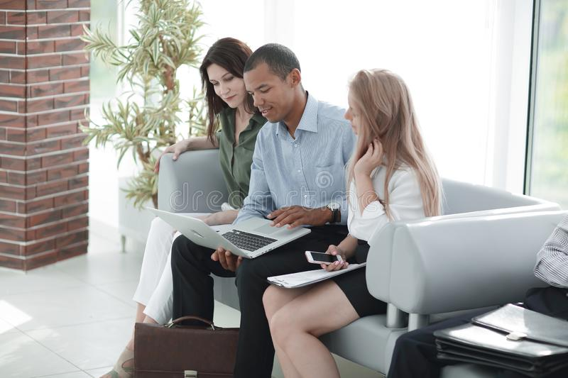 Business group looking at laptop while sitting in the hotel lobby royalty free stock photo