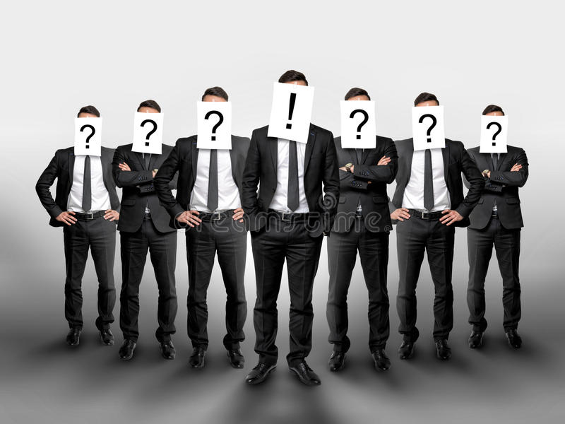 Business group with question marks on their heads and one businessman in the center has exclamation mark. Concept of leadership stock photos
