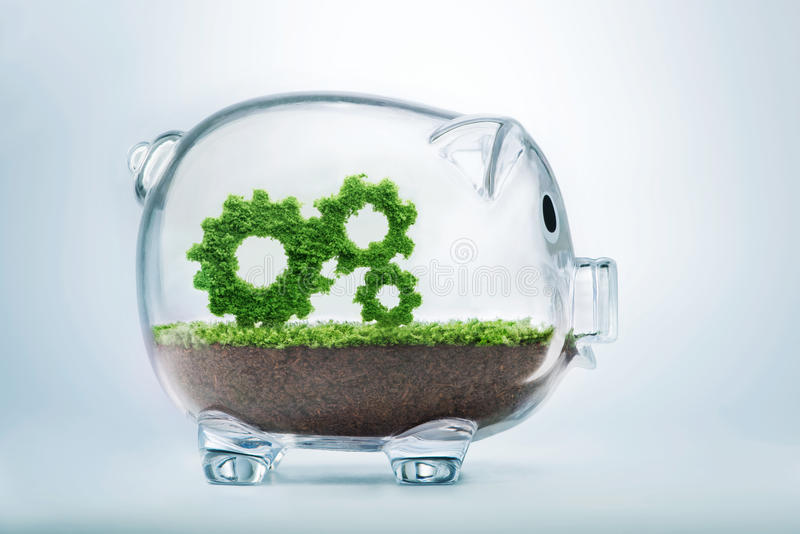 Business growth. Concept with grass growing in shape of gears inside transparent piggy bank royalty free stock image