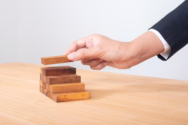 business hand arranging wood block stacking as step stair. Ladder career path concept for business growth success process royalty free stock image