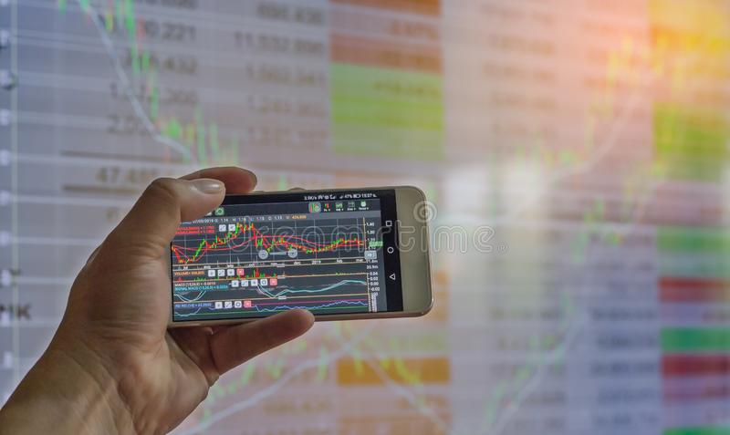 business hand hold and touch screen on smartphone or cellphone over blur stock chart market monitor background,business stock stock images