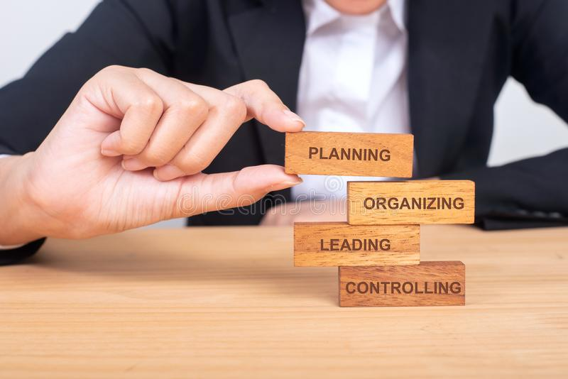 business hand putting the wooden toy with words about four functions of management: Planning, Organizing, Leading and Controlling stock image