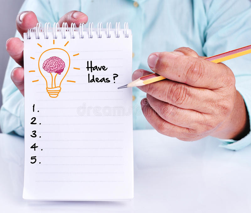 Business hand writing idea or innovation list. On notepad. With lamp of brain icon stock image
