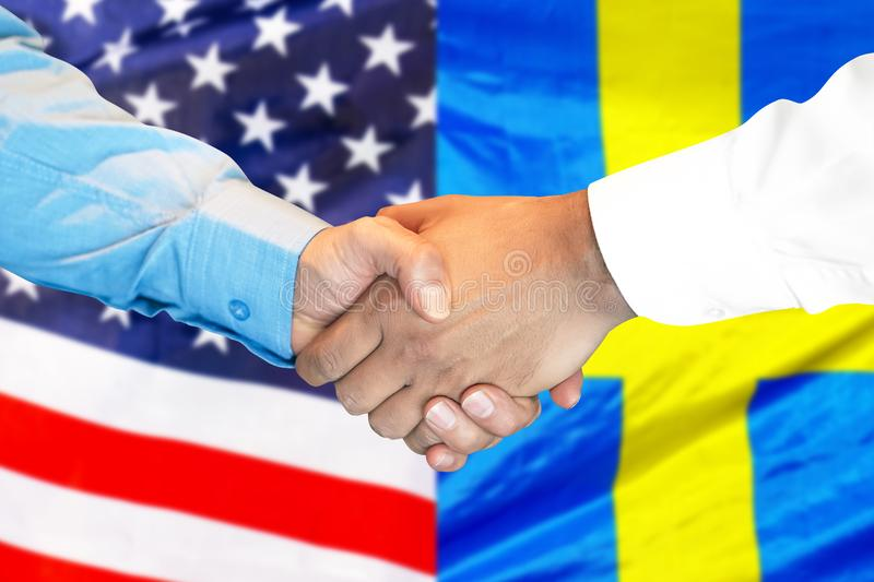 Handshake on american and Swedish flag background stock photography