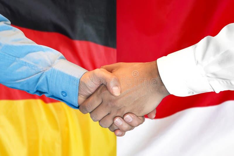 Handshake on Germany and Monaco flag background stock image